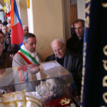 Don Dante Caprioglio e il Sindaco Capra davanti all'urna con le reliquie di San Giovanni Bosco accolta nel Collegio San Carlo di Borgo San Martino